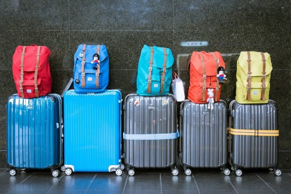 several backpacks and suitcases of varying colours