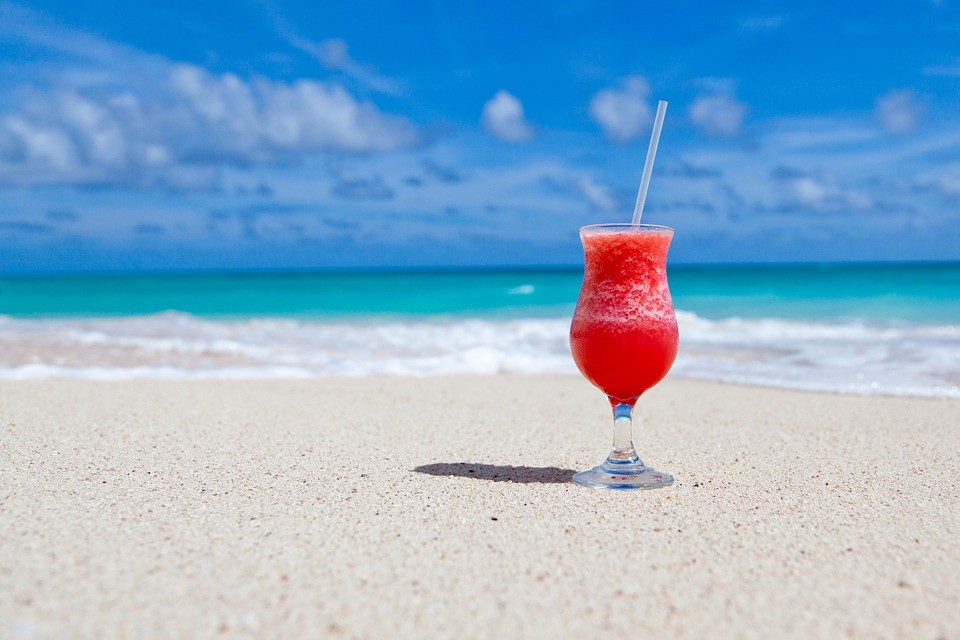 A cocktail placed on the white sands in front of Caribbean blue water